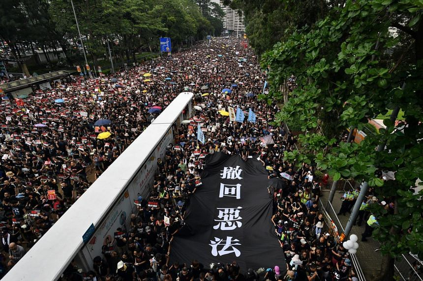 Crowds of protesters clad in black carry a banner against a proposed extradition law on the road outside Victoria Park, on June 16, 2019.
