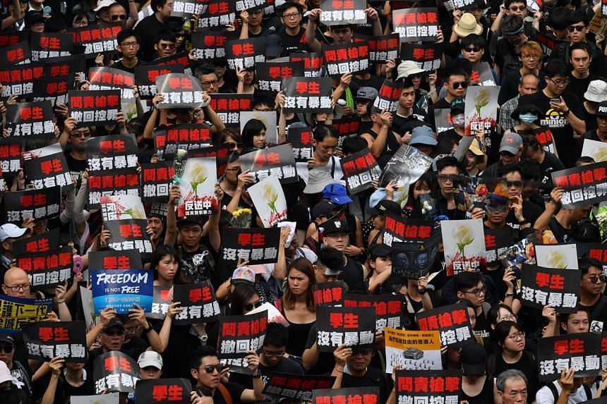 Protesters clad in black holding up placards as they march along the road outside Victoria Park, on June 16, 2019.