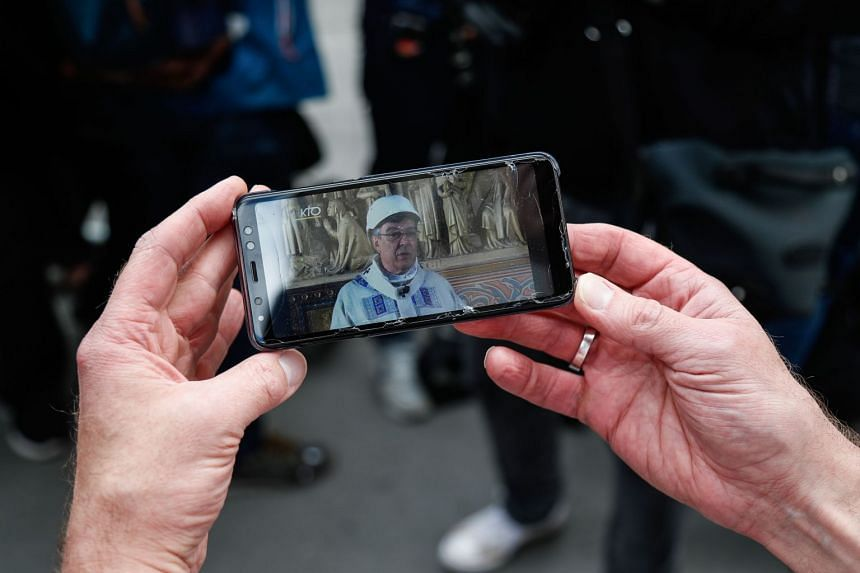 A person holds a mobile phone to watch a live feed of the mass led by Archbishop of Paris Michel Aupetit.