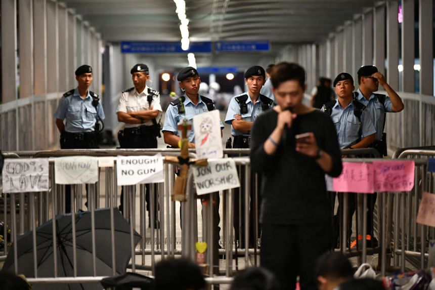 Police officers watch over protesters listening to a rally on a pedestrian bridge near the Legislative Council Complex in Hong Kong on June 15, 2019.