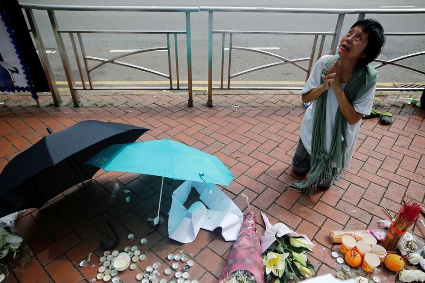 A woman reacts at a site where a man fell from scaffolding at the Pacific Place complex while protesting against a proposed extradition Bill in Hong Kong, on June 16, 2019.
