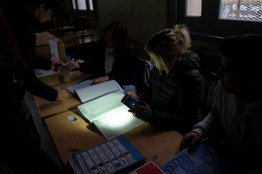 People vote in governor elections during a power outage in Rosario, Argentina.
