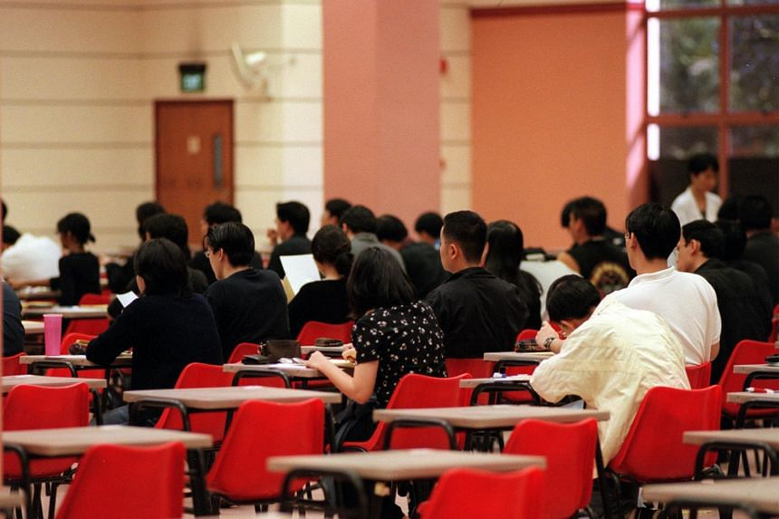 National University of Singapore (NUS) students sitting an exam. Of the six autonomous universities, only NUS and Nanyang Technological University still moderate results using a bell curve for certain modules.