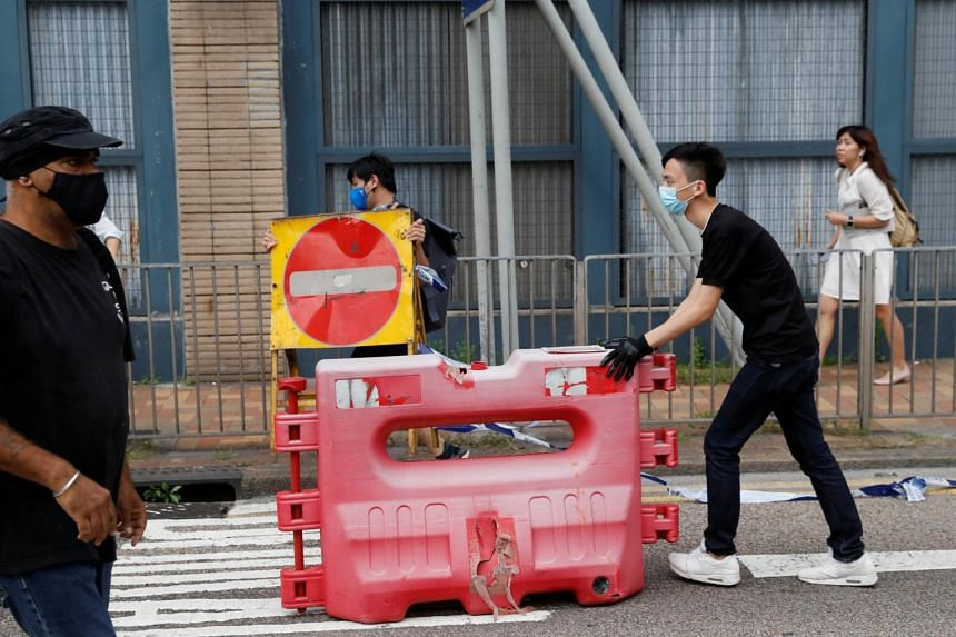Protesters move road barriers during a demonstration against the extradition bill, along a road near the Legislative Council building, in Hong Kong, China on June 17, 2019.