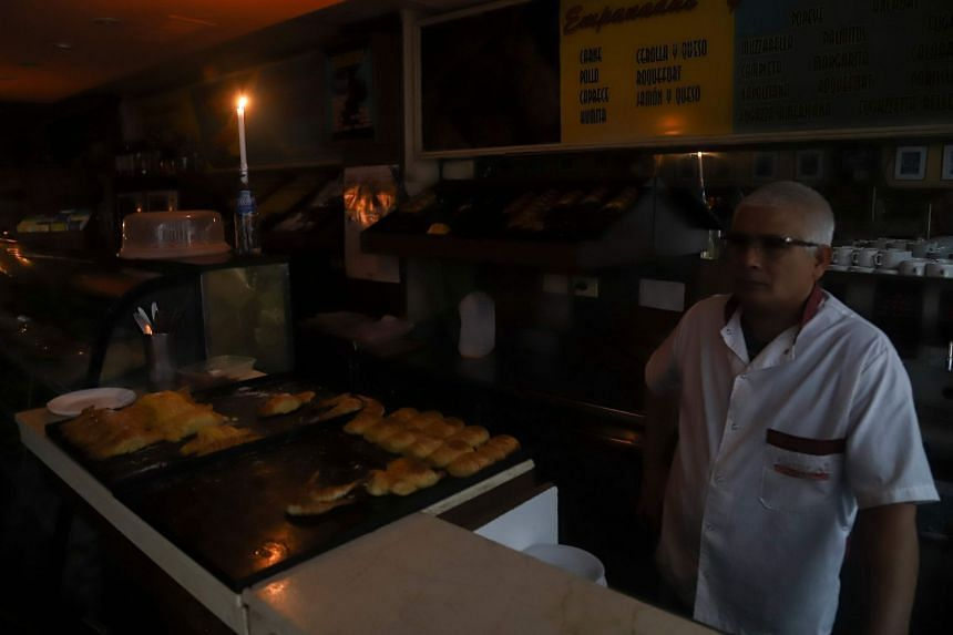 A man working by candlelight at a bakery during the power cut in Buenos Aires.