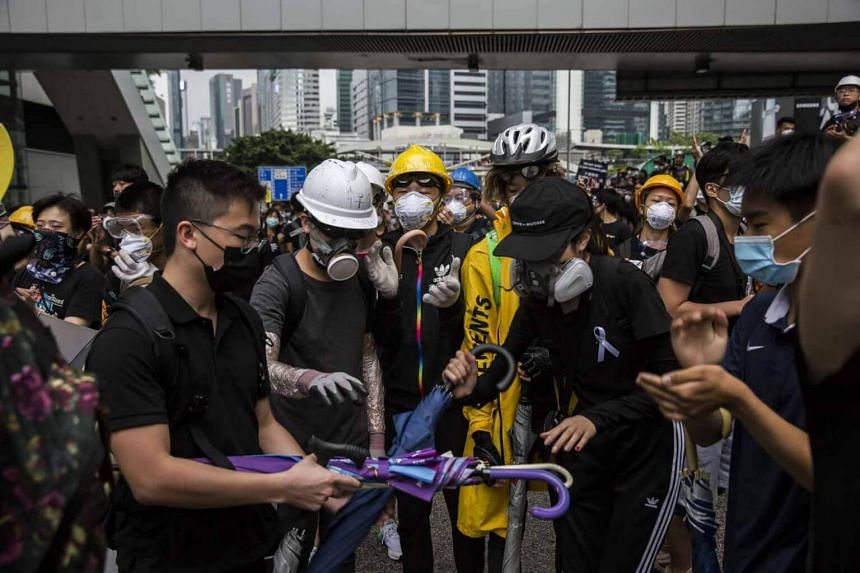Protesters hand out umbrellas to protect against pepper spray while police negotiate to clear roads in Hong Kong early on June 17, 2019.