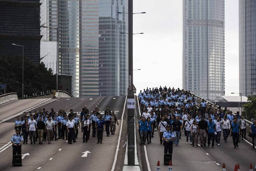 Police arrive to negotiate with protesters to clear a road in Hong Kong early on June 17, 2019.
