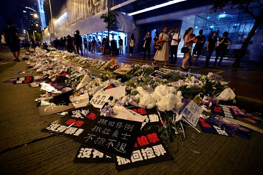 Bouquets of white flowers, written tributes and origami cranes outside Pacific Place on June 16, 2019.