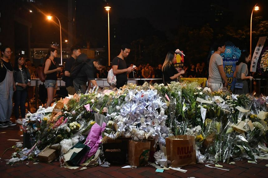Bouquets of white flowers, written tributes and origami cranes and flowers outside Pacific Place on June 16, 2019.