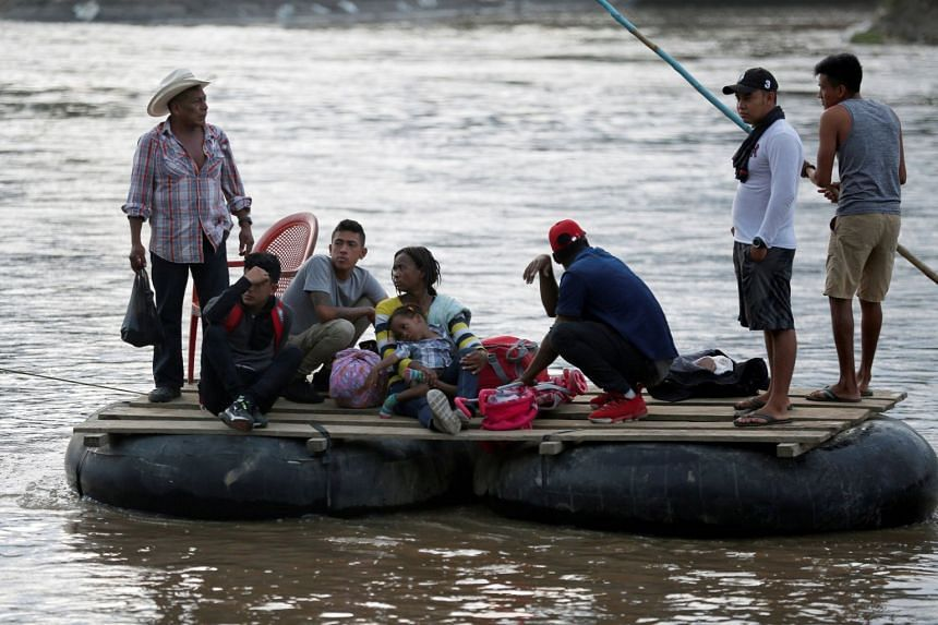 Migrants and locals cross the Suchiate river on a raft from Tecun Uman, in Guatemala, to Ciudad Hidalgo, as seen from Ciudad Hidalgo, Mexico, on June 9, 2019.