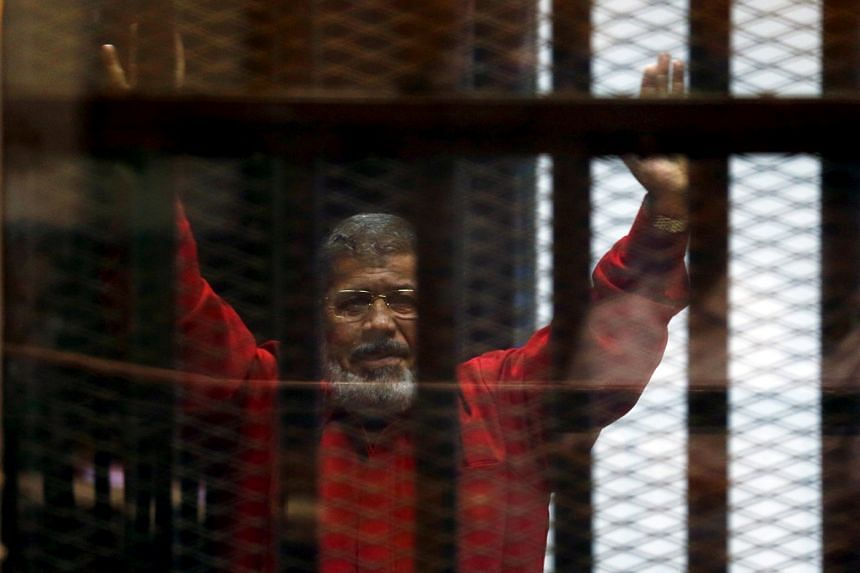 A file photo of Egypt's deposed president Mohamed Mursi greeting his lawyers and people from behind bars at a court wearing the red uniform of a prisoner sentenced to death, during his court appearance with Muslim Brotherhood members on the outskirts