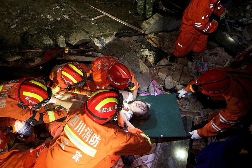 Rescue workers attending to a woman yesterday during rescue operations following the earthquakes in Sichuan province in China. The quakes, about 30 minutes apart, struck late on Monday, with shaking felt in regional cities such as the provincial capi