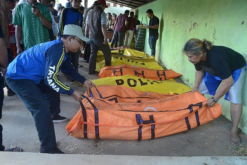 """Men arranging body bags containing victims from a boat that sank with 57 people on board, off Sumenep in East Java province on Monday. """"The boat was hit by a large wave, overturned and sank,"""" said an East Java police spokesman."""