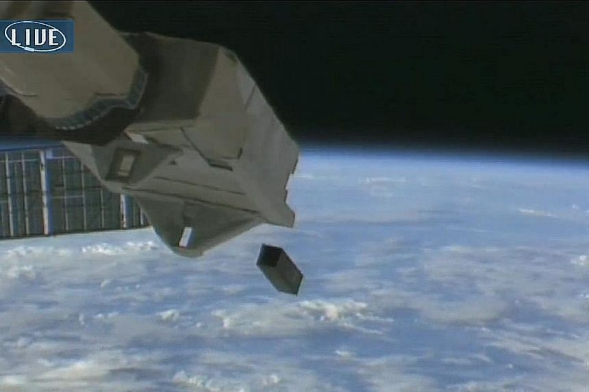 Left: Dr Robert Bedington with a partially assembled SpooQy-1 at the Centre for Quantum Technologies. Above: A live feed from the International Space Station, beamed to the Japan Aerospace Exploration Agency, of SpooQy-1 being deployed into orbit thi