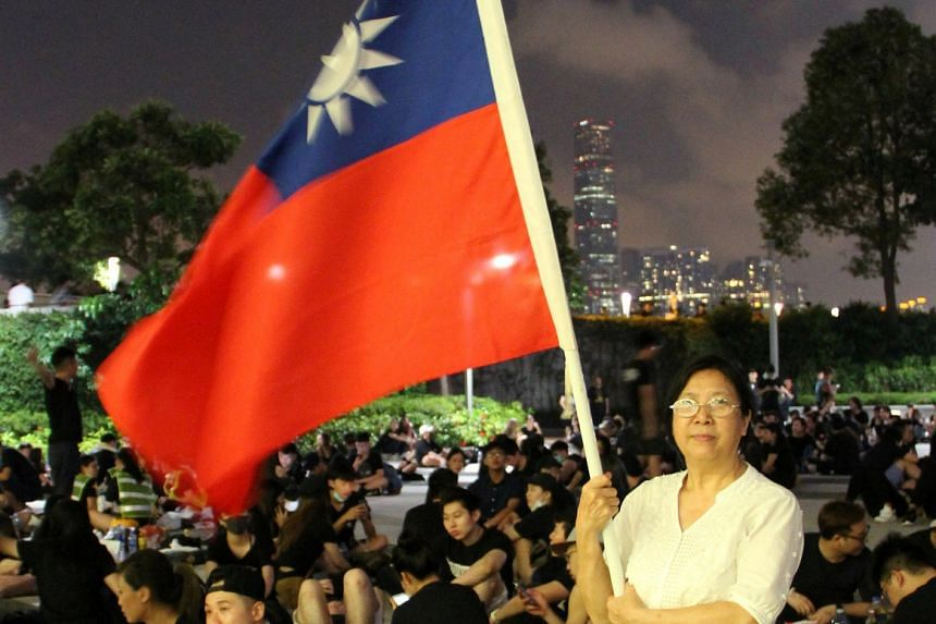 Ms Yung Xiu Kwan, 67, poses with a Taiwan flag during a demonstration against the proposed extradition Bill, in Hong Kong, on June 17, 2019. She is among those leaving the Chinese-ruled city for a new life in proudly democratic Taiwan.