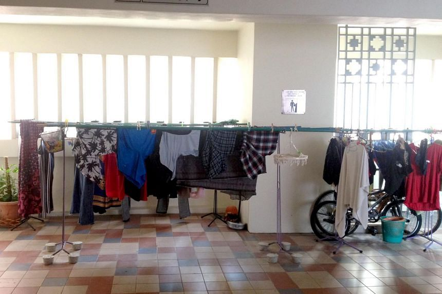 Clothes drying on bamboo poles outside a lift lobby in a Housing Board block at Choa Chu Kang.