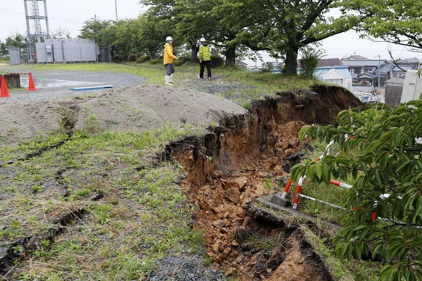 City staff examine the damaged slope after a powerful earthquake hit the northern Japan city on June 19, 2019.