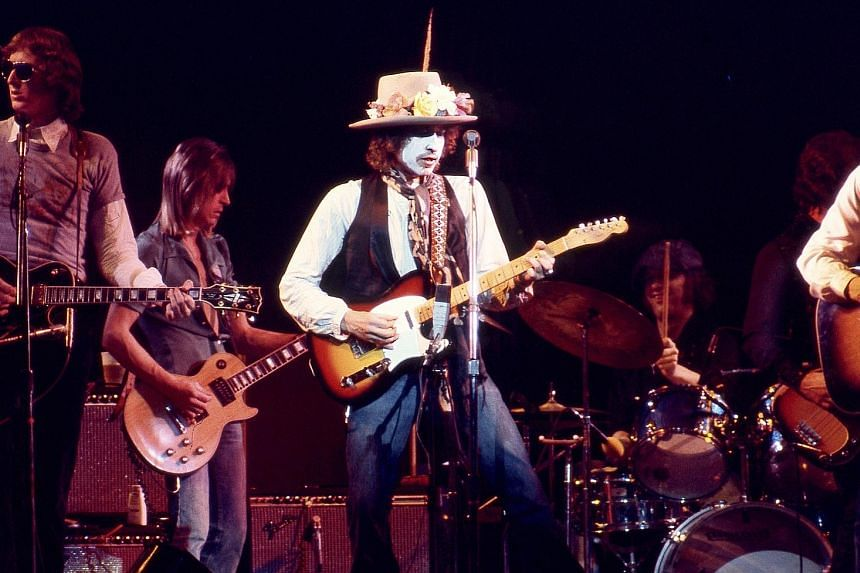 Singer Bob Dylan in white face paint, playing on the Rolling Thunder Revue tour, in the Netflix documentary.