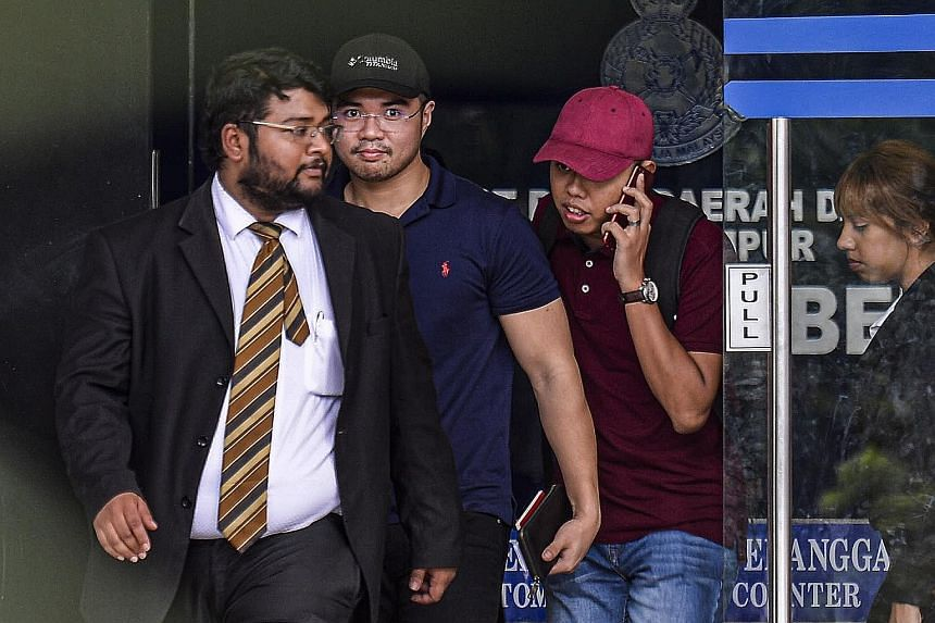 Mr Haziq Aziz (second from left), a PKR youth chief from Santubong in Sarawak, leaving a police station in Kuala Lumpur. He will be given 14 days to reply the show-cause letter.