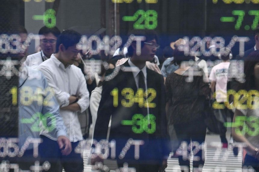 Pedestrians are reflected on an electronics stock indicator at the window of a securities company in Tokyo, on June 3, 2019.