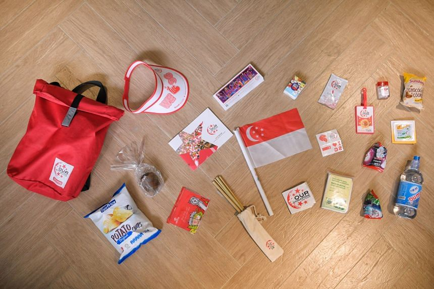 This year's National Day Parade funpack along with its contents, including snacks, mineral water, a souvenir magazine and a discount booklet.