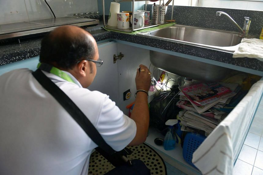 A National Environment Agency officer checks the kitchen cabinet of a home for possible mosquito breeding.