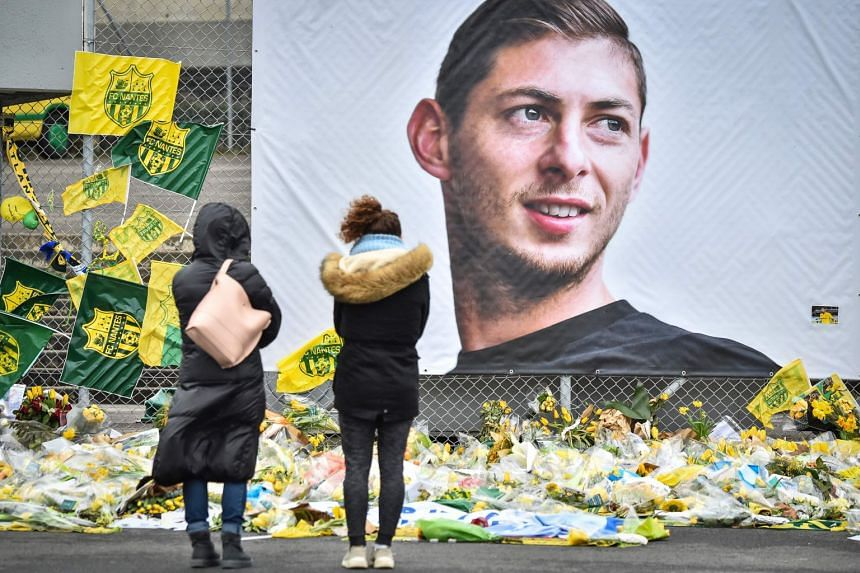 People look at flowers displayed in front of a portrait of Sala at the Beaujoire stadium in Nantes.