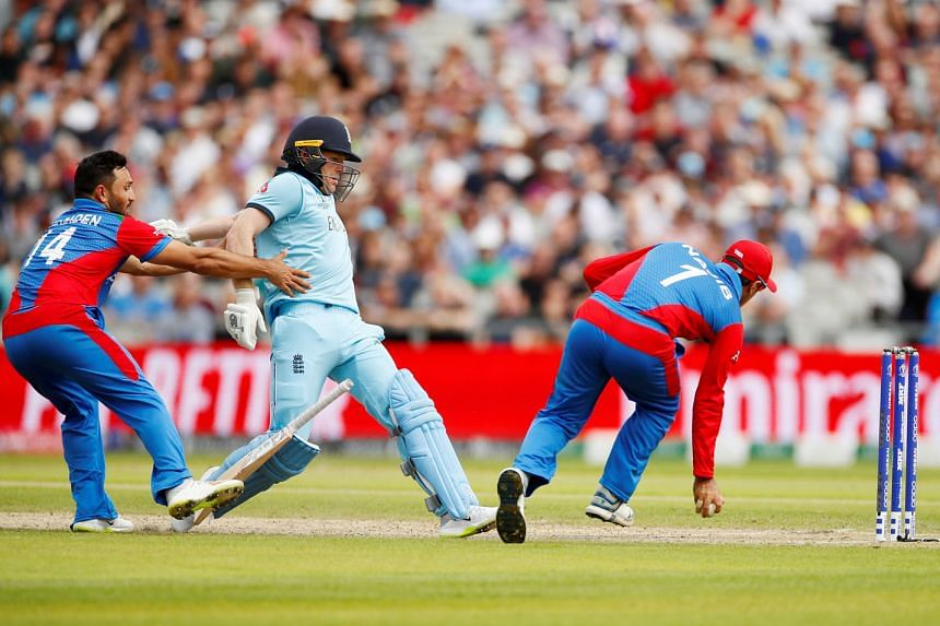 Afghanistan's Gulbadin Naib (left) trying to pull back England batsman Eoin Morgan during their match in Manchester on Tuesday. England won by 150 runs to top the standings. PHOTO: REUTERS