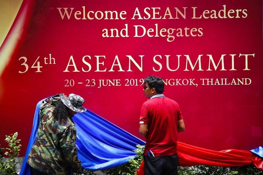 Workers adorn a large poster welcoming Asean leaders to the 34th Asean Summit in Bangkok, Thailand.