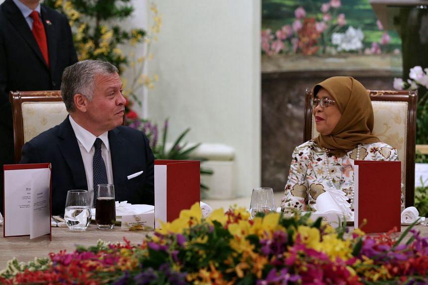 President Halimah Yacob speaking with Jordan's King Abdullah II during a state banquet at the Istana.