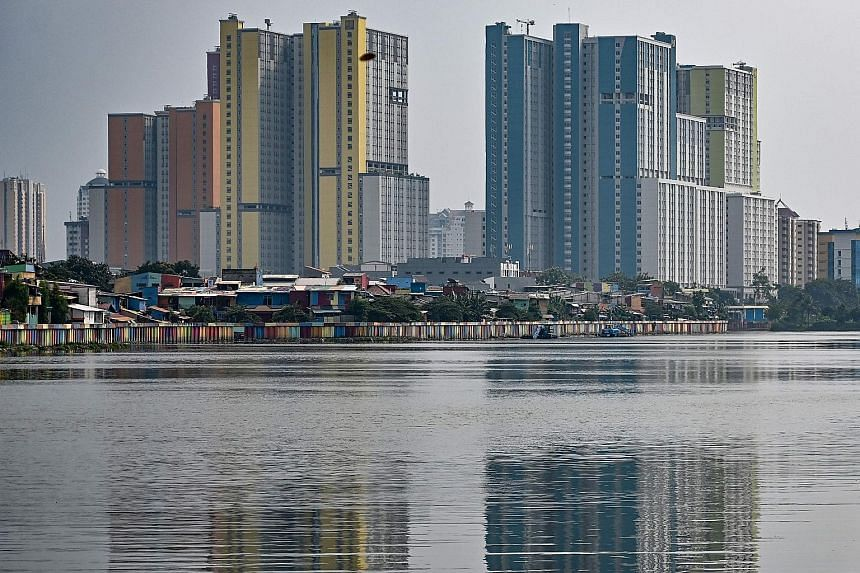 A slum area in Jakarta, dwarfed by high-rise buildings. Indonesian Finance Minister Sri Mulyani Indrawati has said the government's 5.3 per cent growth target may not be achieved. Analysts say fiscal stimulus may be more effective at keeping Indonesi