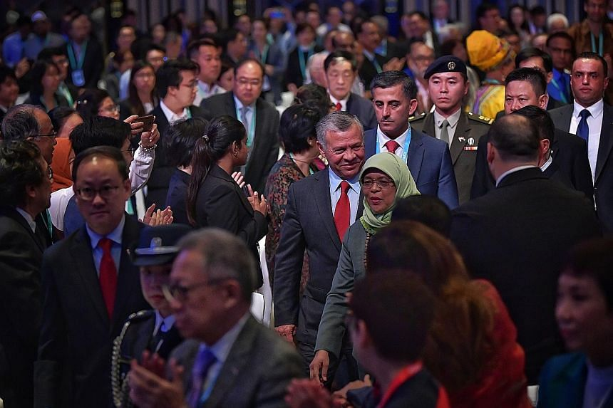 Jordan's King Abdullah II and President Halimah Yacob arriving at the inaugural International Conference on Cohesive Societies at the Raffles City Convention Centre yesterday. The King called on the billions of people who seek peace and harmony to ra