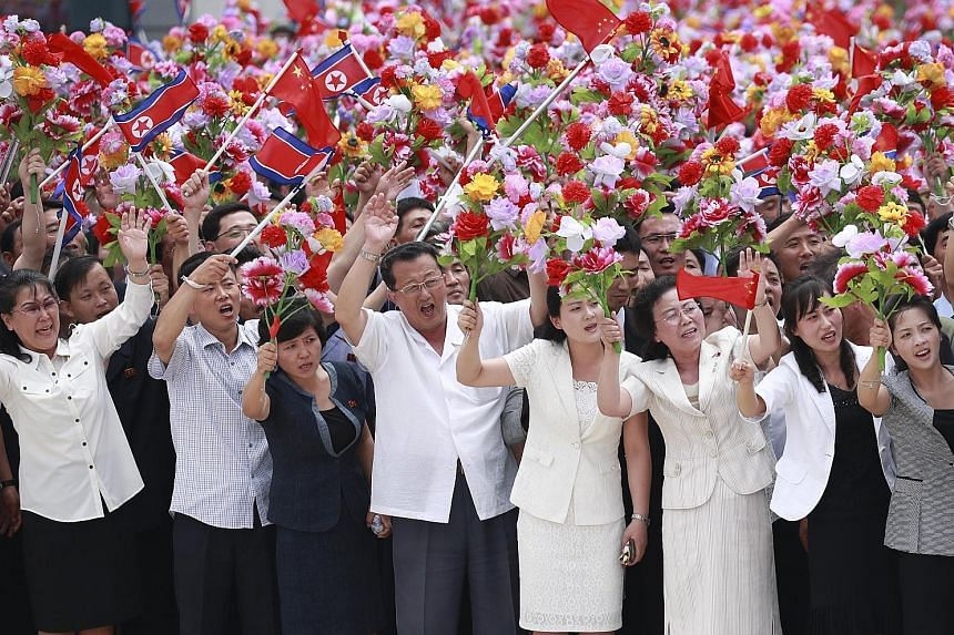 North Koreans giving a warm welcome to Chinese President Xi Jinping on his arrival at Pyongyang airport yesterday. PHOTO: XINHUA