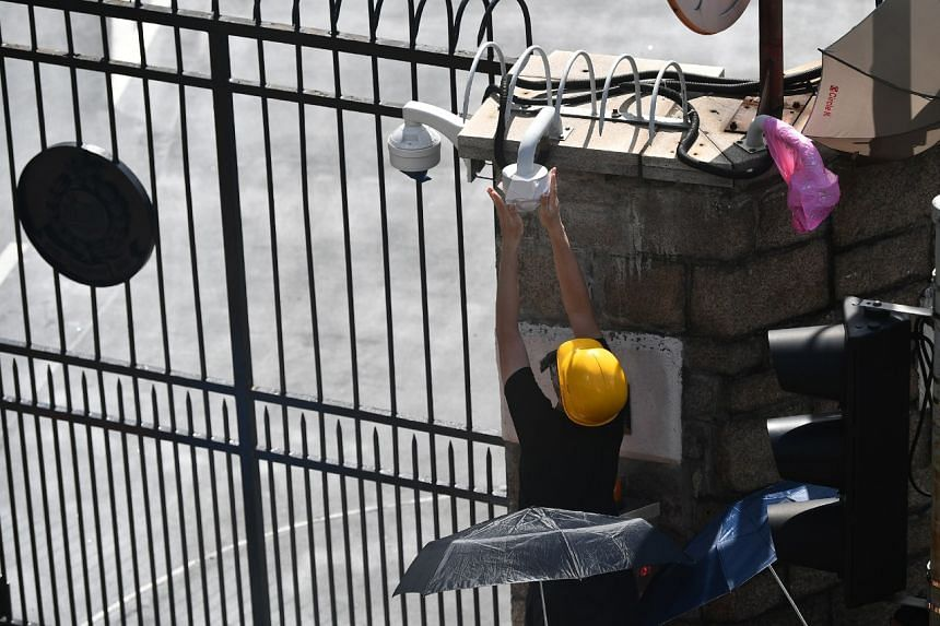 A protester covering the CCTV cameras outside Hong Kong's police headquarters on June 21, 2019. ST PHOTO: LIM YAOHUI