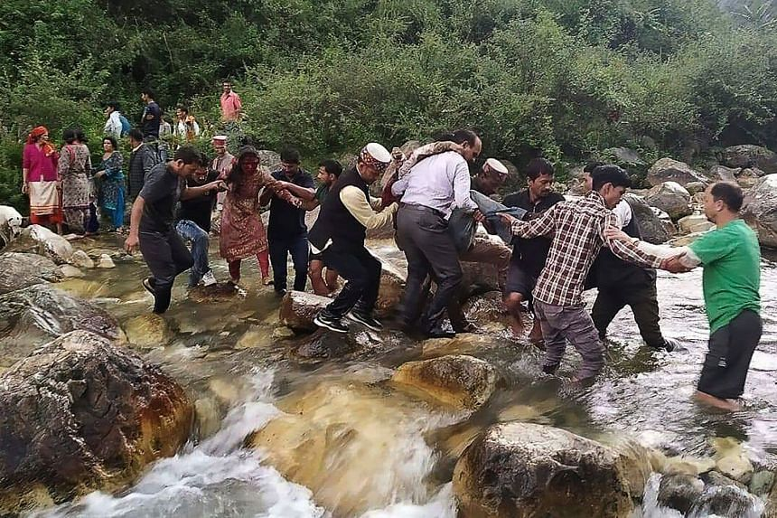 Local residents help accident survivors cross a river after a bus carrying some 50 passengers fell into a 150m gorge.