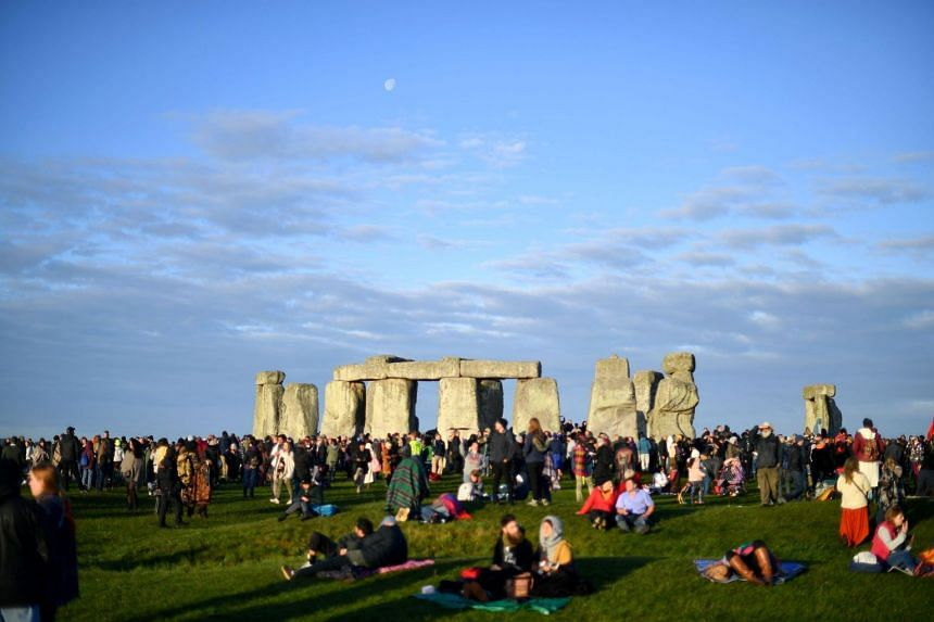 The crowd, dressed warmly against the chilly temperatures, cheered and clapped as the sun rose over the horizon while pagans, including a bearded druid in white robes and an elaborate headdress made of flowers and branches, performed rituals.