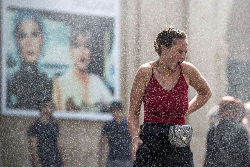 A woman is sprayed with water to cool down as temperature hit 33 deg C in Prague, Czech Republic, June 12 2019.