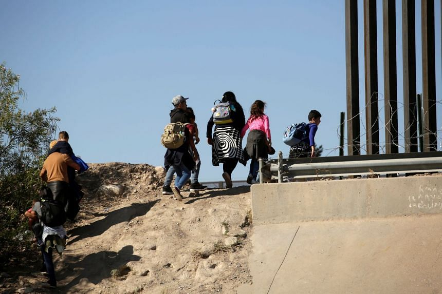 Migrants are seen after crossing illegally into El Paso, Texas, on June 19, 2019.