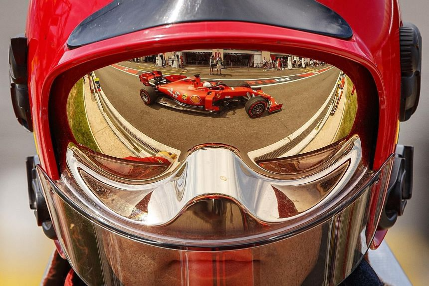 Sebastian Vettel's Ferrari is reflected on the helmet of a marshal during the first practice session of the French Formula One Grand Prix at the Paul Ricard Circuit.