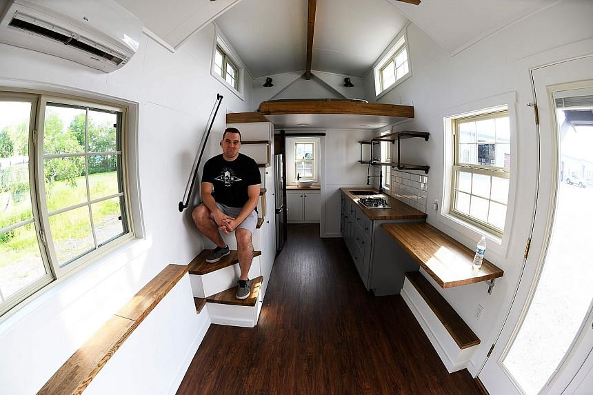 Liberation Tiny Homes' sales and marketing director Marcus Stoltzfus (above) in a unit; and home owners Melissa and Scott Berrier in their 34 sq m home, which they moved into about four months ago.