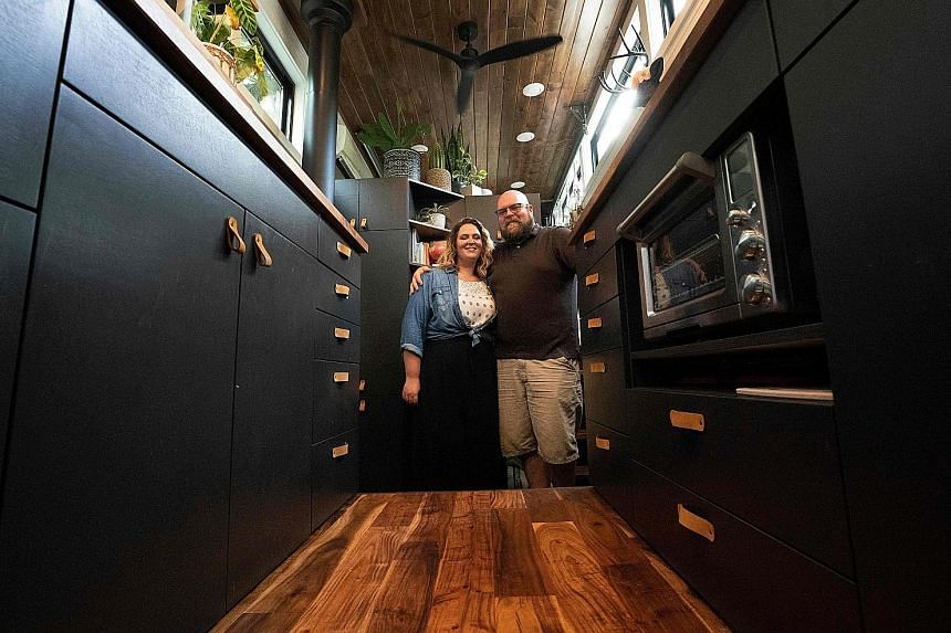 Liberation Tiny Homes' sales and marketing director Marcus Stoltzfus in a unit; and home owners Melissa and Scott Berrier (both above) in their 34 sq m home, which they moved into about four months ago.