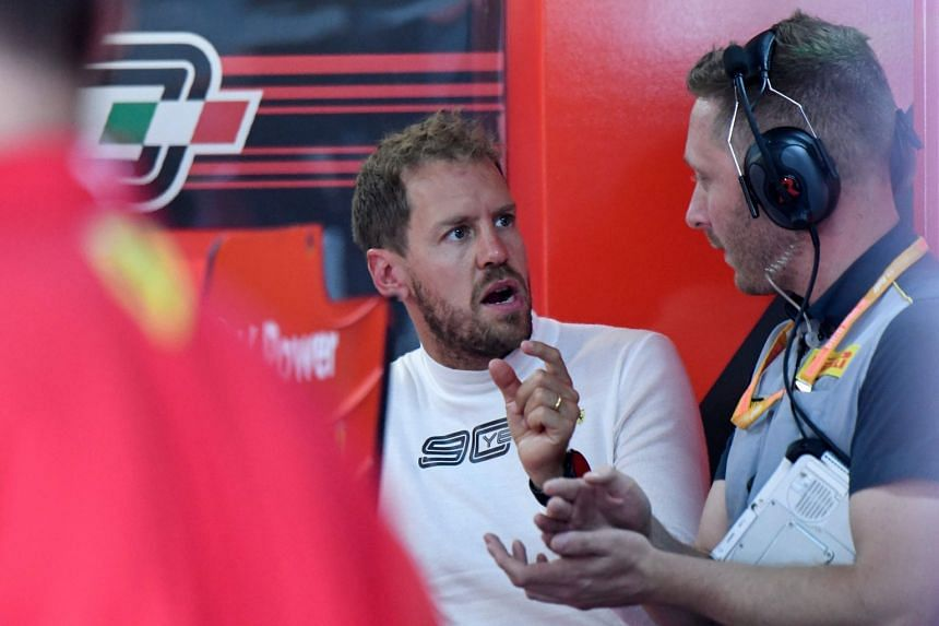 Vettel speaks with a technician in the pits during the first practice session for the French grand prix.