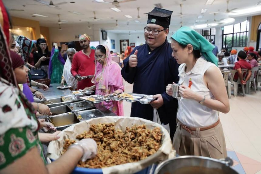 Taoist priest-in-training Kendrick Goh with a fellow participant, Ms Gwee Siew Theng, at the Silat Road Sikh Temple.