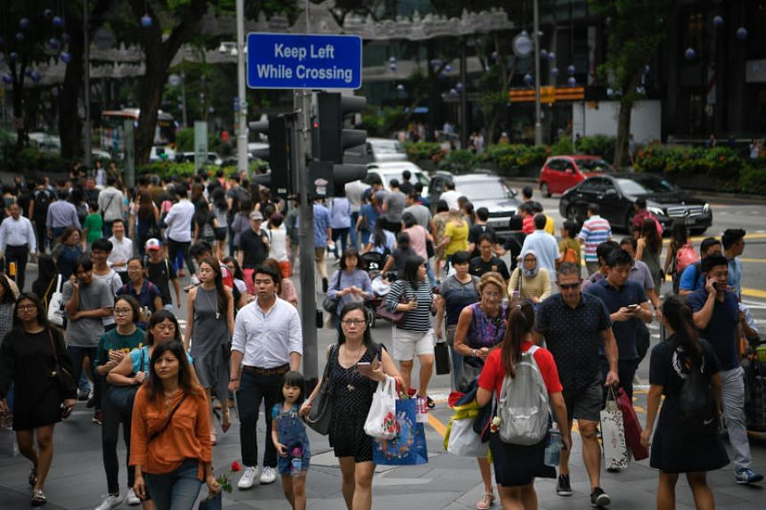 People walk across a busy junction of Cairnhill Road and Orchard Road on Nov 24, 2017.