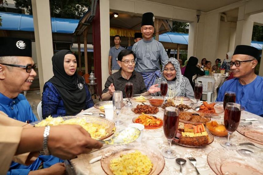 Deputy Prime Minister Heng Swee Keat at a Hari Raya open house and dinner hosted by Madam Ratnah Mohari (second from right) and her husband Abas Abdul Rahman (standing) at the void deck of their Tampines flat on June 22, 2019.