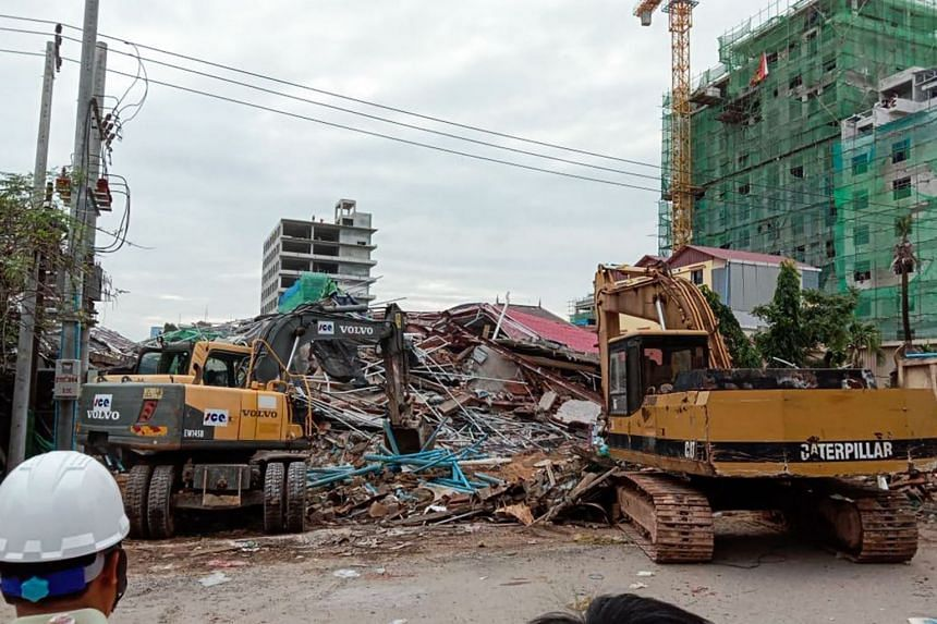 Rescue workers clearing debris after a building collapsed at a construction site in Sihanoukville on June 22, 2019.