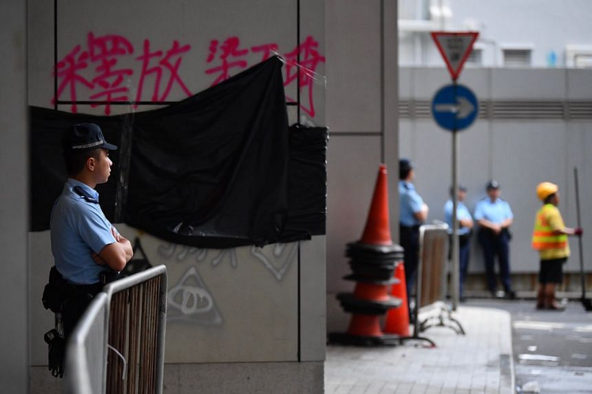 Officers use pieces of black plastic to cover up graffiti on the walls outside Hong Kong's police headquarters on June 22, 2019.