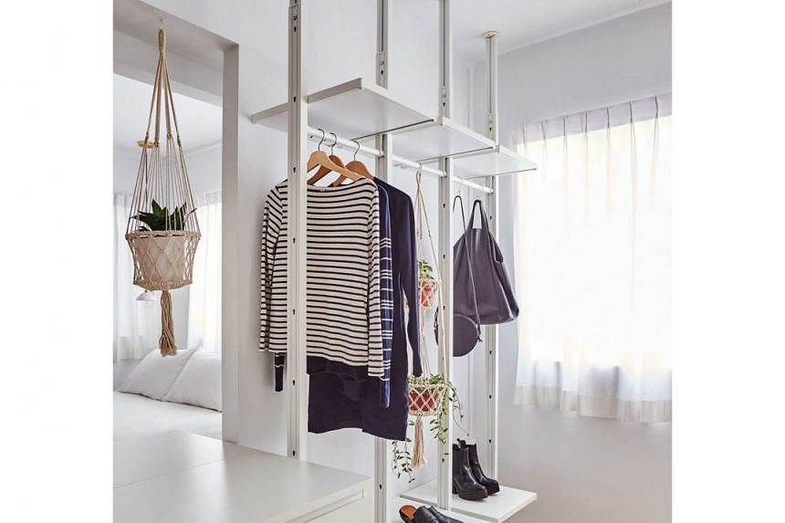 A partial wall separates the walk-in wardrobe from the sleeping area, lending each space privacy.