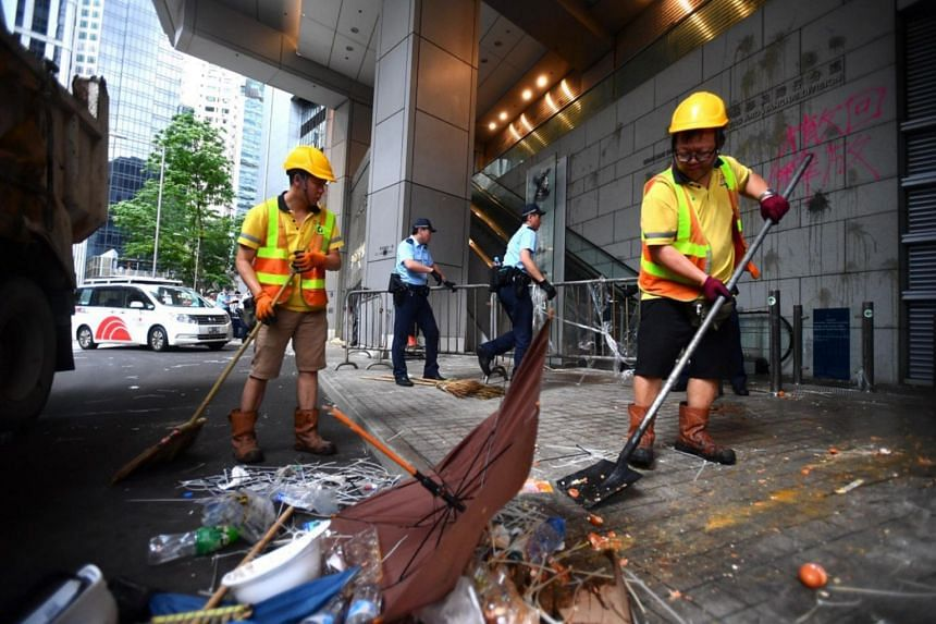 Cleaners and police staff cleaning up the area around Hong Kong police headquarters on June 22, 2019. Barricades and trash are cleared while graffiti is taped over with black plastic.