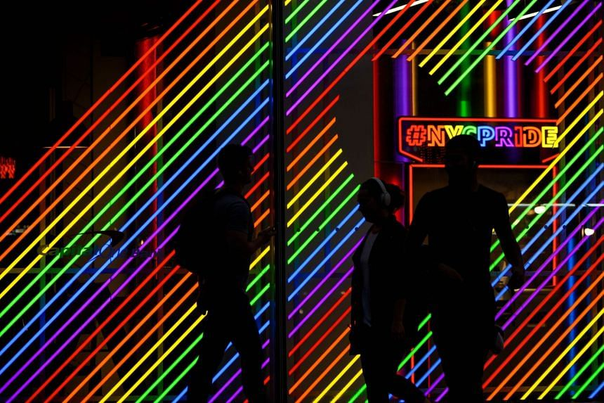 People walk past rainbow-coloured lights outside a building in New York City.